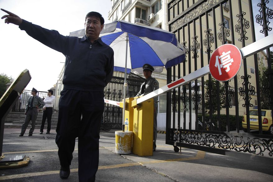 A plainclothes security man tells a photographer to move away from the gates to a residential compound where Liu Xia, the wife of 2010 Nobel Peace Prize winner Liu Xiaobo, is held under house arrest in Beijing on Tuesday, Oct. 12, 2010. (AP Photo/Ng Han Guan)