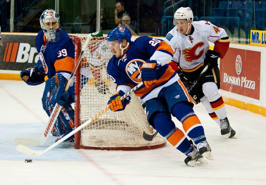 ASSOCIATED PRESS New York Islanders defensemen James Wisniewski rounds his net as Calgary Flames forward Greg Nemisz trails during the first period of a preseason NHL hockey game in Saskatoon, Saskatchewan, on Wednesday, Sept. 29, 2010.