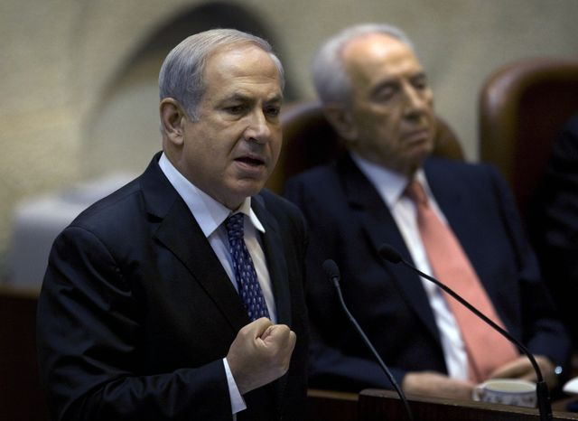 Israeli President Shimon Peres (right) listens as Prime Minister Benjamin Netanyahu speaks at the opening of the winter session in the Knesset, Israel's parliament, in Jerusalem on Monday, Oct. 11, 2010. Mr. Netanyahu offered to renew a moratorium on Jewish settlement construction in the West Bank but only if the Palestinians meet his demand to recognize Israel as a Jewish state. (AP Photo/Sebastian Scheiner)