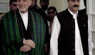 Pakistani Prime Minister Yousuf Raza Gilani (right) escorts Afghan President Hamid Karazi for bilateral talks in Islamabad, Pakistan, on Thursday, Sept. 16, 2010. (AP Photo/B.K. Bangash)