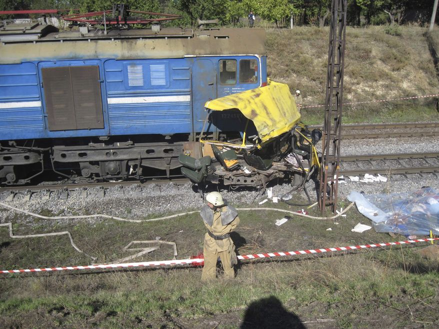 The remains of a bus lie next to a railway train at the site of an accident outside the town of Marhanets, Ukraine, on Tuesday, Oct. 12, 2010. The crowded passenger bus collided with the train in eastern Ukraine, killing at least 43 people and leaving 8 injured, police said. (AP Photo/Emergency Situations Ministry)