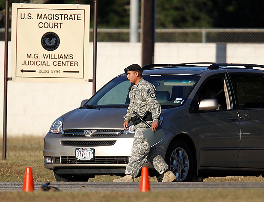Military police check a vehicle outside the U.S. Magistrate court where an Article 32 hearing for Maj. Nidal Malik Hasan is scheduled to be held, Tuesday, Oct. 12, 2010 in Fort Hood, Texas. Hasan, 40, is charged with premeditated murder and attempted premeditated murder in a Nov. 5 attack , which killed 13 people and wounded 32 others in a processing center where soldiers were making final preparations to deploy. The Article 32 hearing will determine whether there is enough evidence to put the Army psychiatrist on trial. (AP Photo/Eric Gay)
