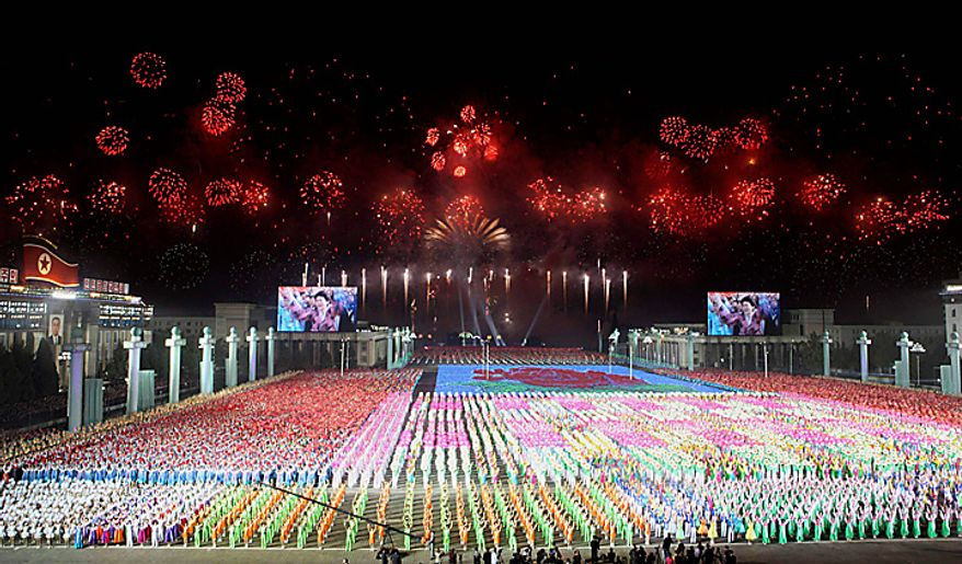 In this photo released by China's Xinhua News Agency, North Koreans perform as fireworks explode during an evening celebration marking the 65th anniversary of the communist nation's ruling Workers' Party in Pyongyang, North Korea on Sunday, Oct. 10, 2010. (AP Photo/Xinhua, Yao Dawei)