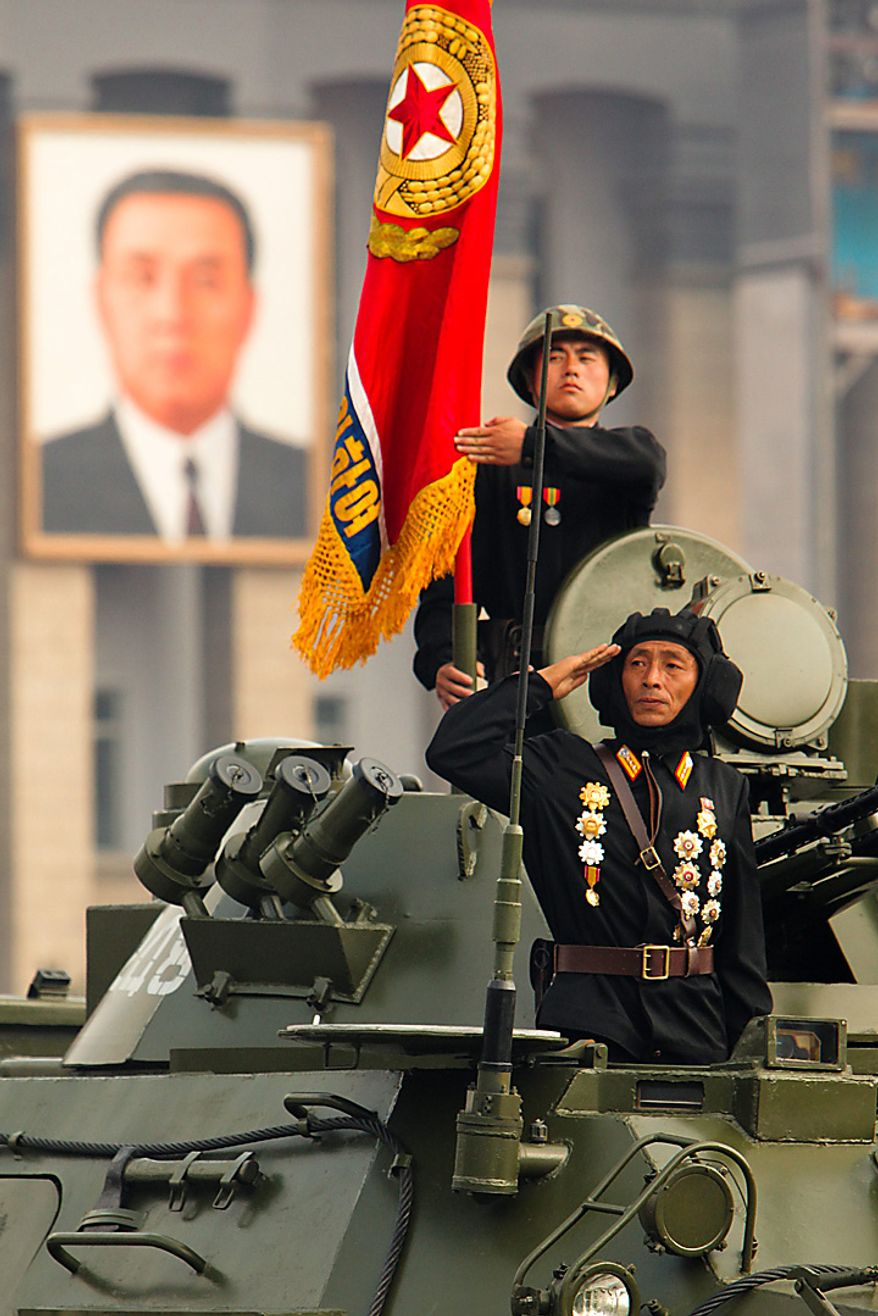 Members of the North Korean military salute during a parade commemorating the 65th anniversary of the Korea Worker's Party in Pyongyang, North Korea, on Sunday, Oct. 10, 2010. North Korean heir apparent Kim Jong Un stood at his father's right side today as they reviewed troops, tanks and missiles in a Pyongyang military parade. Photographer: Dieter Depypere/Bloomberg