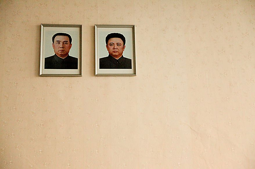 A portrait of Kim Il Sung, founder of North Korea, left, and Kim Jong Il, leader of North Korea, hangs at Sunan International Airport in Pyongyang, North Korea, on Monday, Oct. 11, 2010. North Korean heir apparent Kim Jong Un stood at his father's right side today as they reviewed troops, tanks and missiles in a Pyongyang military parade. Photographer: Dieter Depypere/Bloomberg