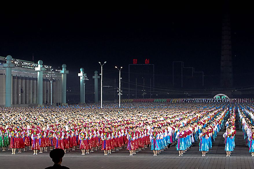 Performers dance in Kim Il Sung square during a ceremony commemorating the 65th anniversary of the Korea Worker's Party in Pyongyang, North Korea, on Sunday, Oct. 10, 2010. North Korean heir apparent Kim Jong Un stood at his father's right side today as they reviewed troops, tanks and missiles in a Pyongyang military parade. Photographer: Dieter Depypere/Bloomberg