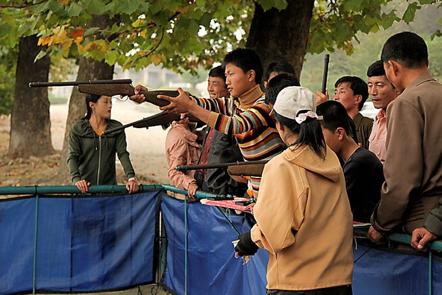 A man aims an air-rifle at game booth in a park in Pyongyang, North Korea, on Monday, Oct. 11, 2010. North Korean heir apparent Kim Jong Un stood at his father's right side today as they reviewed troops, tanks and missiles in a Pyongyang military parade. Photographer: Dieter Depypere/Bloomberg