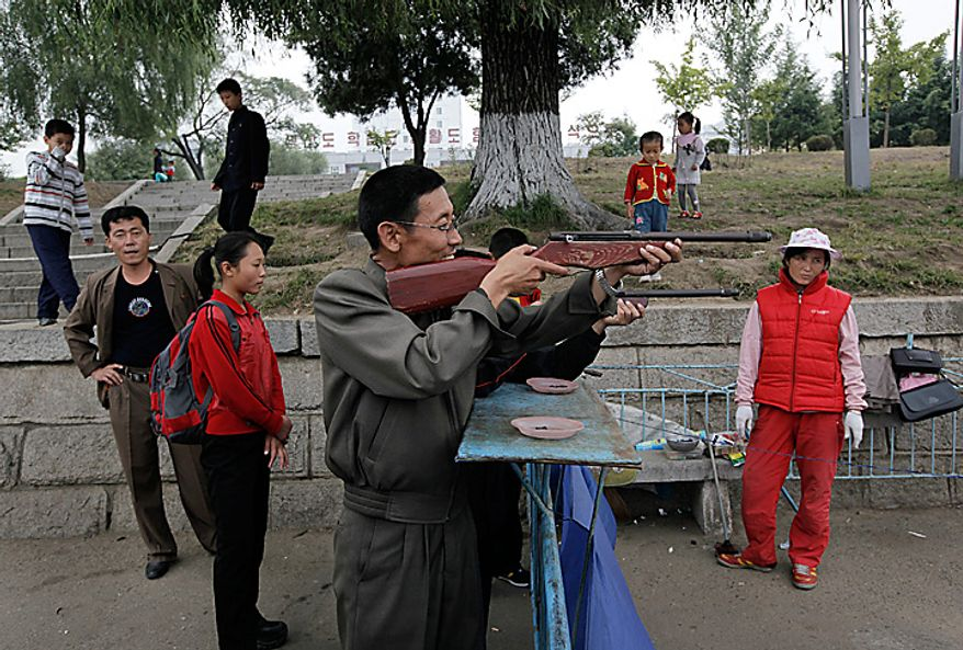A North Korean man plays a shooting game at a booth along the Taedong River in Pyongyang, North Korea on Monday, Oct. 11, 2010. The party in Pyongyang stretched into Monday as North Koreans took the day off to celebrate a major political anniversary and to revel in the unveiling of leader Kim Jong Il's heir-apparent, son Kim Jong Un. (AP Photo/Vincent Yu)