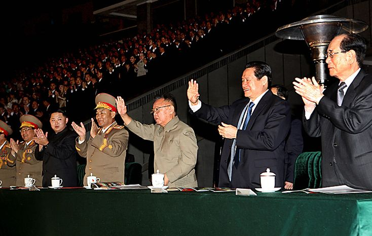 In this photo taken on Saturday, Oct. 9, 2010 released by China's Xinhua News Agency, North Korean leader Kim Jong Il, thrid from right,and  Zhou Yongkang, second from right, a member of China's Politburo, wave as they watch the Arirang mass games performance staged to celebrate the 65th anniversary of the founding of the Workers' Party of Korea (WPK) in Pyongyang, North Korea. Accompanying them are: Kim Jong Un, second from left in dark suit, the third son of Kim Jong Il, and Kim Yong Nam, right, the president of the country's parliament. (AP Photo/Xinhua, Yao Dawei)