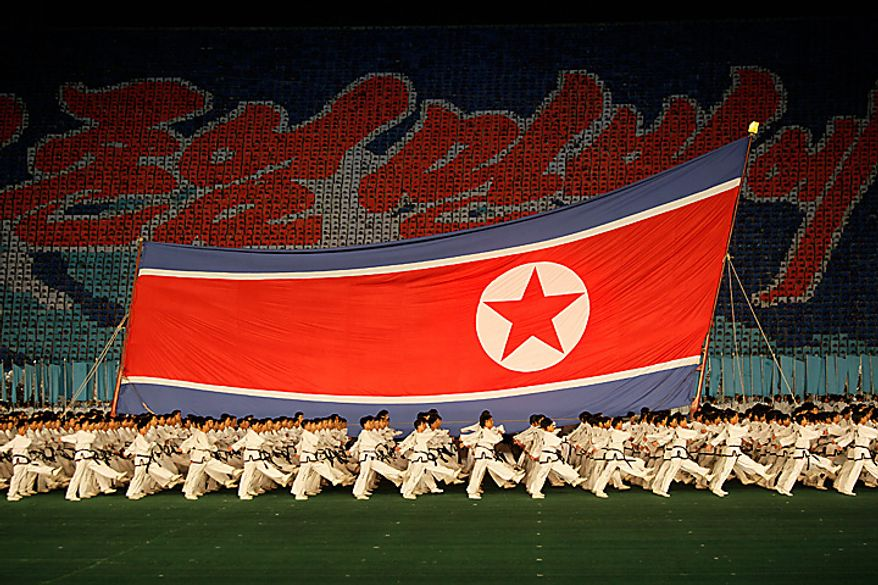 North Korea dancers perform in front of a North Korea nation flag during a Arirang mass games to mark the  65th anniversary of the communist nation's ruling Workers' Party in Pyongyang, North Korea on Saturday, Oct. 9, 2010. Leader Kim Jong Il brought dancers at the Arirang mass games to tears Saturday by making a rare appearance at the festival on the second day of celebrations in the North Korean capital. (AP Photo/Vincent Yu)
