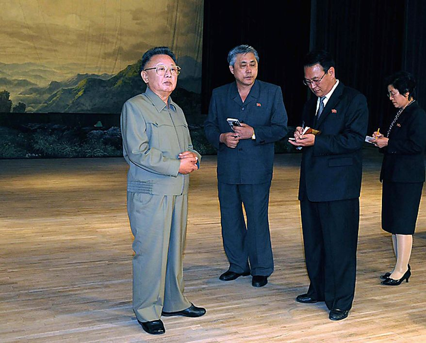 In this undated photo released by Korean Central News Agency via Korea News Service Saturday, Oct. 9, 2010, North Korean leader Kim Jong Il, left, stands on the stage during his inspection of the newly-built State Theater in Pyongyang, North Korea's capital. (AP Photo/Korean Central News Agency via Korea News Service)