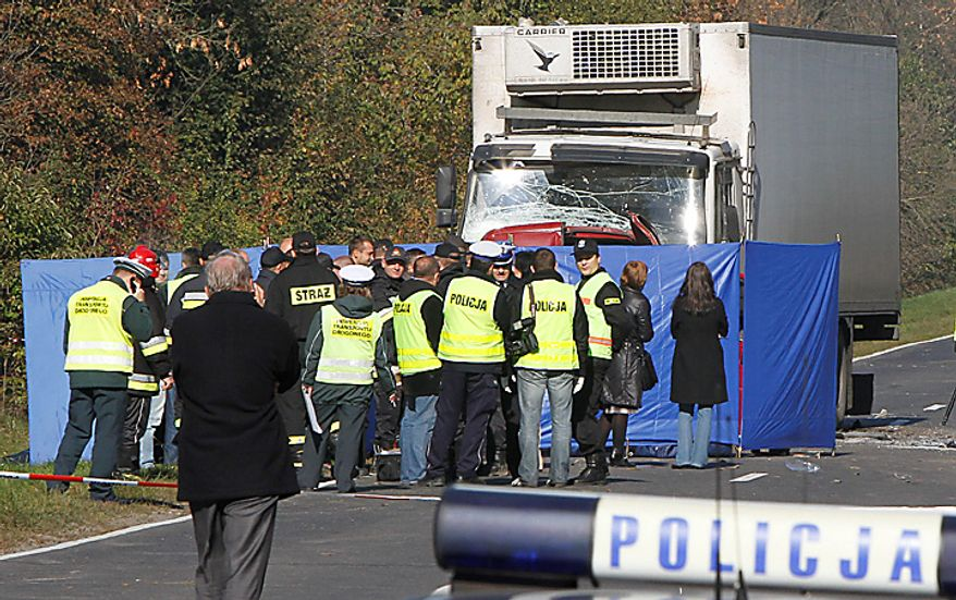Police officers stand in front of a screen that hides from view a van and a truck which collided near Nowe Miasto in central Poland killing 18 people early Tuesday, Oct. 12, 2010. Police say the cargo van carrying orchard workers was apparently trying to overtake in dense fog when it crashed head-on with the truck, killing all 17 passengers and the driver. The truck driver was injured. (AP Photo/Czarek Sokolowski)