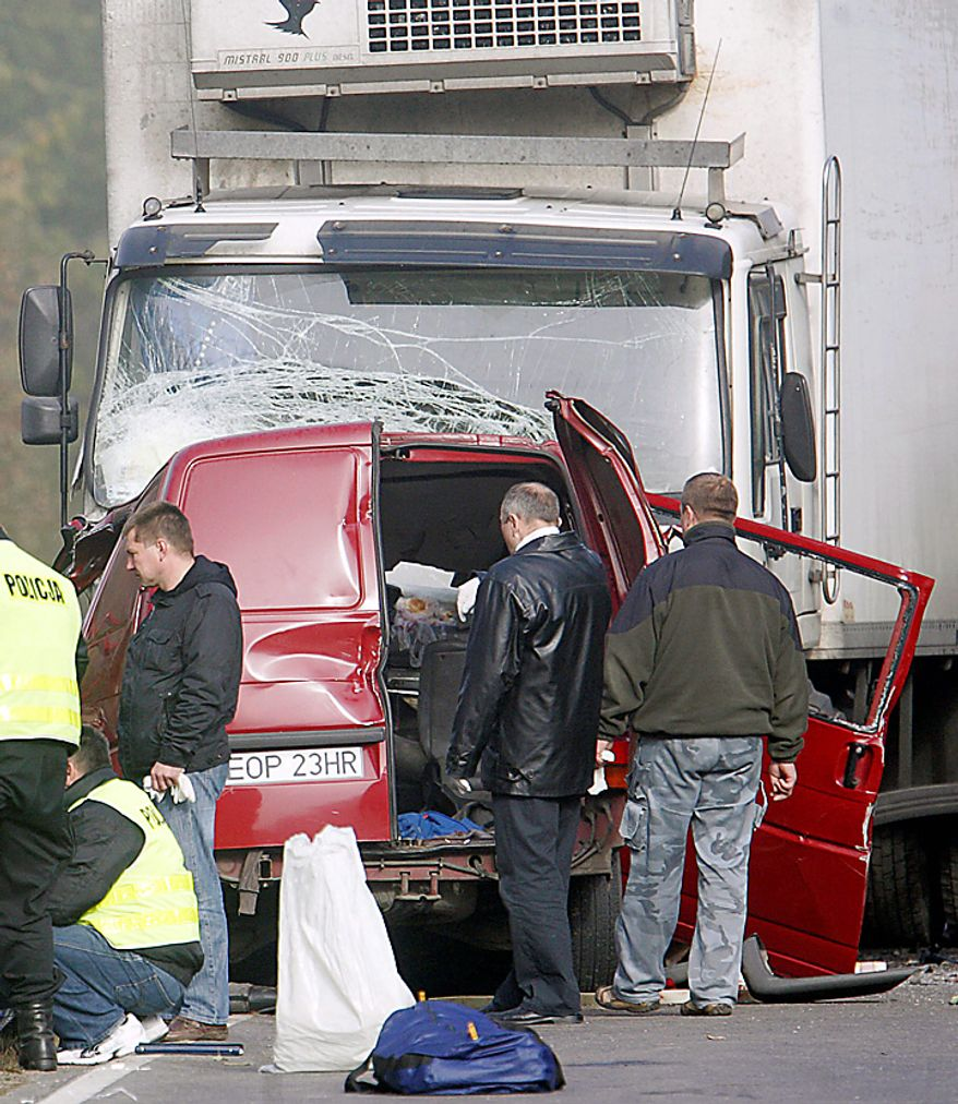 Police work at the site where a van carrying seasonal orchard workers crashed head-on with a truck while apparently trying to overtake in dense fog near Nowe Miasto in central Poland, killing all 17 passengers and the driver, early Tuesday, Oct.12, 2010. The truck driver was injured. (AP Photo/str)