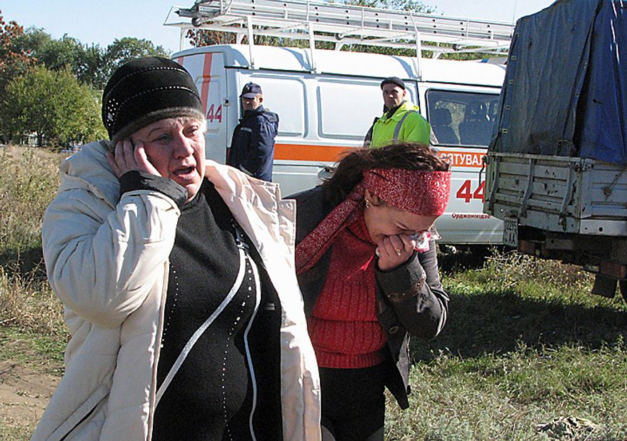 People react at the scene of an accident outside the town of Marhanets, Ukraine, Tuesday, Oct. 12, 2010 after a bus attempted to cross the track, ignoring a siren that indicated an oncoming train. At least 40 people were killed officials at the Ministry of Emergency Situations said. Another eleven people were injured. Road and railway accidents are common in Ukraine, where the roads are in poor condition, vehicles are poorly maintained, and drivers and passengers routinely disregard safety and traffic rules. (AP Photo)