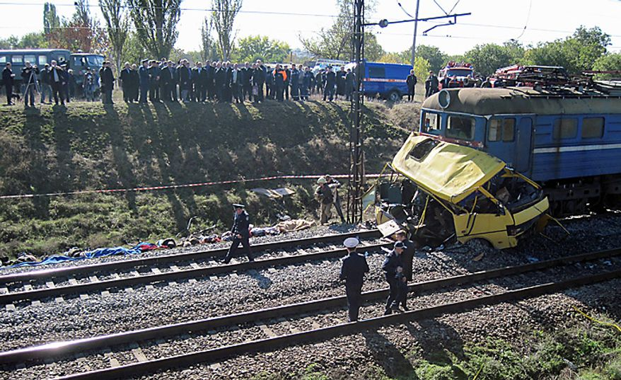 The remains of a bus lay next to a railway train at the site of an accident outside the town of Marhanets, Ukraine, Tuesday, Oct. 12, 2010. the crowded passenger bus collided with a train in eastern Ukraine Tuesday, killing 40 people and leaving 11 in critical condition, police said. The Interior Ministry said that the collision occurred outside the town of Marhanets in the Dnipropetrovsk region after the bus attempted to cross the track, ignoring a siren that indicated an oncoming train.Thirty-seven people from the bus died on the spot and another person died later in the hospital. There were no injuries reported on the train.(AP Photo)