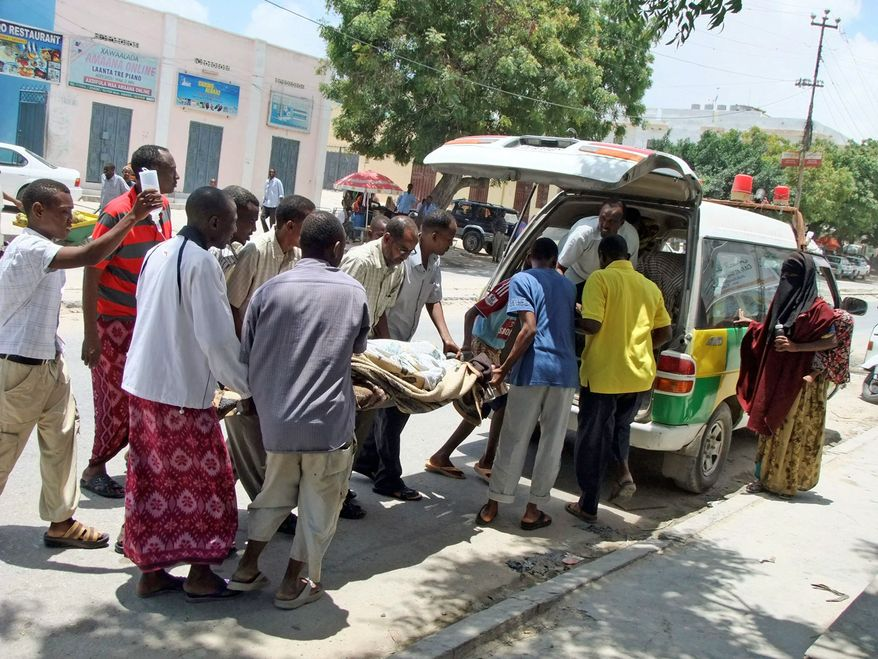 Local people help load an injured person into the back of a van that serves as an ambulance in Mogadishu, where violence between militants and pro-government forces has raged for almost 20 years. The ambulances are poorly supplied, and neither drivers nor their assistants have medical training. (Associated Press)