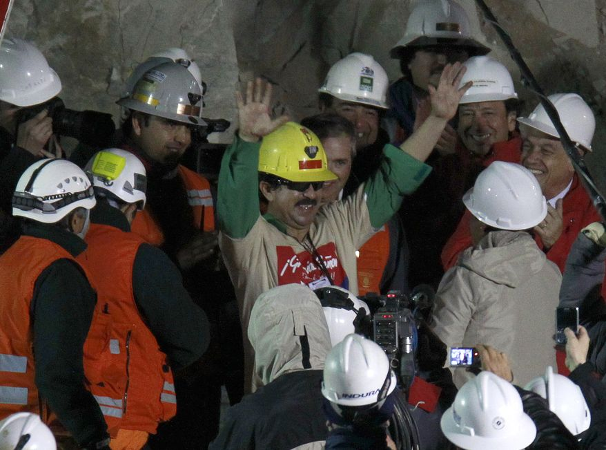 Rescued miner Juan Andres Illanes Palma salutes Wednesday at his arrival to the surface from a collapsed San Jose gold and copper mine near Copiapo, Chile, where he and 32 other miners were trapped for more than two months. Palma was the third miner to be rescued. (Associated Press)