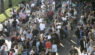 In this Sept. 30, 2010, photo, thousands of people wait in line at the Los Angeles Convention Center for free mortgage help. (AP Photo/Nick Ut)