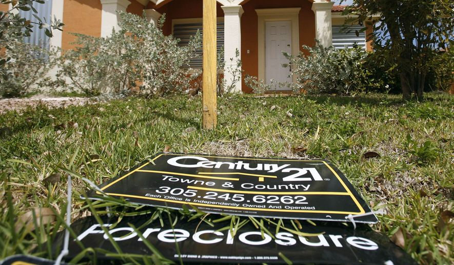 In this March 24, 2009, file photo, a sign lies on the ground in front of a foreclosed home in Homestead, Fla. Officials in 50 states and the District of Columbia launched a joint investigation Oct. 13, 2010, into allegations that mortgage companies mishandled documents and broke laws in foreclosing on hundreds of thousands of homeowners. (AP Photo/J Pat Carter, File)