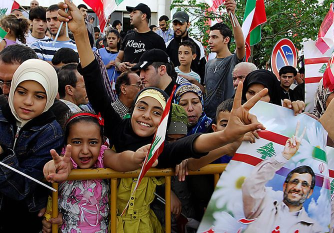 ** FILE ** Children flash the victory sign as people line the streets to welcome Iranian President Mahmoud Ahmadinejad on the highway leading to Beirut Airport, Lebanon, Wednesday, Oct. 13, 2010. (AP Photo/Mahmoud Tawil)