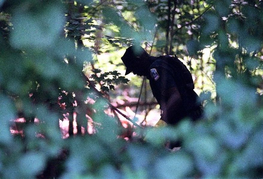 Police search for clues in Rock Creek Park in 2001. (The Washington Times)
