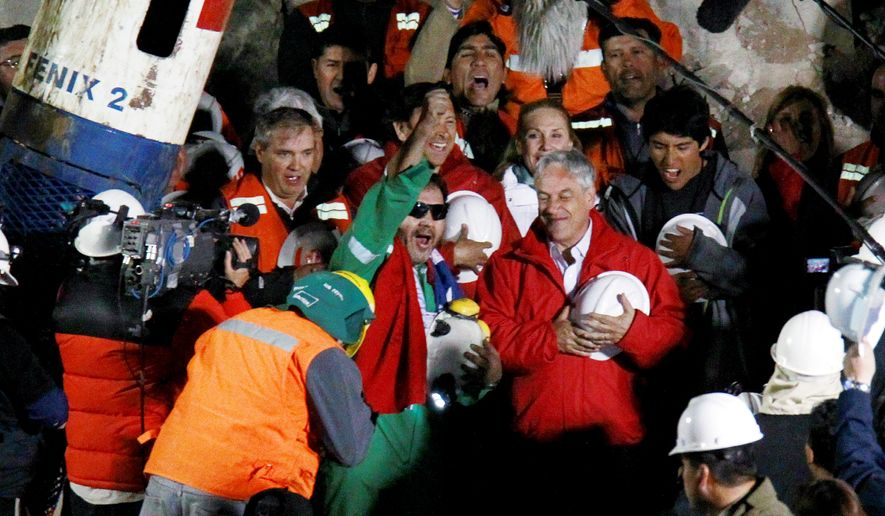 FREE AT LAST! Luis Urzua, the last of the 33 miners to be rescued from a collapsed mine near Copapio, Chile, celebrates next to Chilean President Sebastian Pinera Wednesday. The miners were trapped underground for 69 days. (Associated Press)
