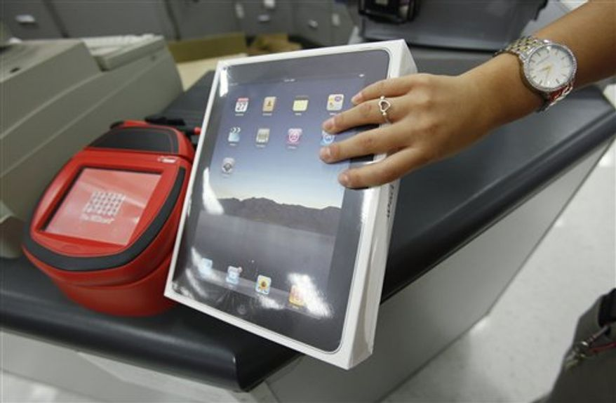 In this Oct. 3, 2010 photo, a customer purchases an a Apple iPad at a Target store in Cupertino, Calif. Apple's shares topped $300 for the first time Wednesday, Oct. 13, as stellar iPad sales and a planned expansion into China continued to give investors high hopes for the iPhone maker's already healthy prospects. (AP Photo/Paul Sakuma)
