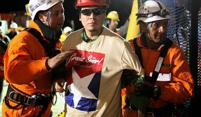 In this photo released by the Chilean government, miner Pedro Cortez, center, is helped by rescue workers after being pulled out of the San Jose gold and copper mine where he had been trapped with 32 other miners for over two months near Copiapo, Chile, Wednesday Oct. 13, 2010.  (AP Photo/Chilean Government, Hugo Infante)