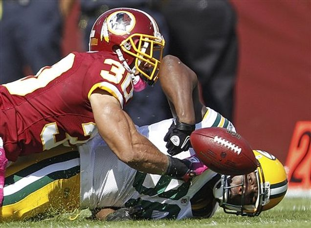 Green Bay Packers' Donald Lee fumbles the ball on a hit from Washington Redskins safety LaRon Landry during the first half of an NFL football game in Landover, Md., Sunday, Oct. 10, 2010. Washington recovered, and Packers' Jermichael Finley left the game with an injury suffered later on the play. (AP Photo/Evan Vucci)