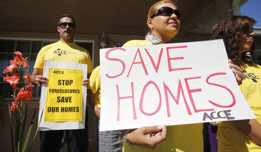 **FILE** In this photo from Sept. 24, 2010, supporter Marisa Salas (right) holds a sign during a foreclosure and eviction rally at the home of Carlos Moreno in Menlo Park, Calif. Moreno has owned his home since 2006, had his home under foreclosure since January 2010, and was served eviction notice in July 2010. His case is now pending with the bank. (Associated Press)