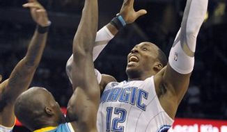 Orlando Magic center Dwight Howard, left, blocks a pass by New Orleans Hornets guard Chris Paul during the first half of a preseason NBA basketball game in Orlando, Fla., Sunday, Oct. 10, 2010. (AP Photo/Phelan M. Ebenhack)