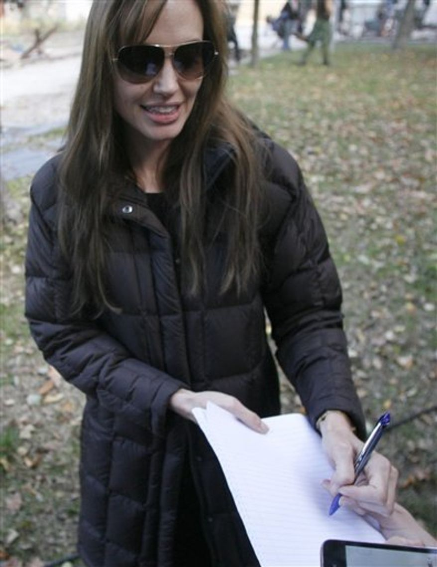 FILE - US actress Angelina Jolie signs autographs for fans during the shooting of her directorial debut, a film called 'Untitled Bosnian War Love Story' in Budapest, Hungary, in this Wednesday, Oct. 13, 2010 file photo. Bosnian authorities have denied Jolie a permit to shoot her directorial film debut in the country amid protests by rape victims who object to its alleged subject matter. J olie's Sarajevo  producer, Edin Sarkic,  said  Friday  Oct 15 2010 that the rumors were not true. He says he has re-submitted the application and sent the film's full script to Sarajevo's  Culture Minister and expects to get a permit. (AP Photo/MTI, Bea Kallos, Pool, file)