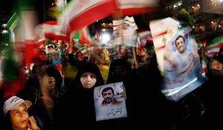Hezbollah supporters hold up posters of Iranian President Mahmoud Ahmadinejad before his speech in Lebanon Wednesday. His fierce opposition to Israel is popular. (Associated Press)