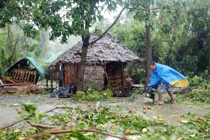 A local man in Cauayan in the northeastern Philippines prepares Monday to cut and remove trees downed by Super Typhoon Megi, which cut off power, phone and Internet service and was accompanied by huge waves and near-zero visibility. (Associated Press)