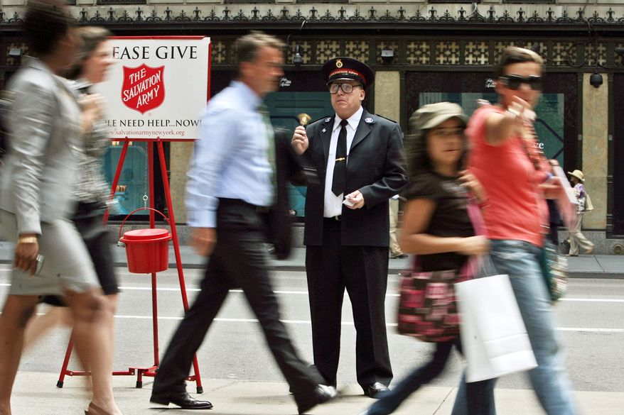 Salvation Army worker Daniel Aherns, here in July 2009, collects on Fifth Avenue at Rockefeller Center in New York. A seasonal stereotype doesn't keep the charity from helping those hardest hit by the recession. (Associated Press)
