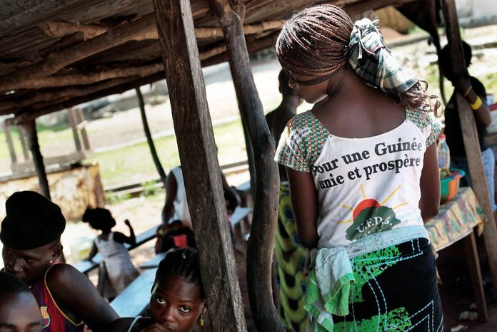 """A Guinean woman on the shore of the Rio Pongo river wears a shirt reading: """"For a unified and prosperous Guinea."""" The date for the second round of elections has been delayed multiple times. (Associated Press)"""