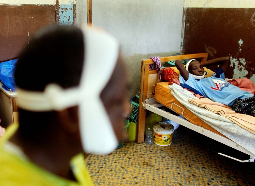The hospital bed next to Mr. Diallo holds Mory Keita. He was hit in the face by a rock at the party headquarters of a Malinke candidate in what was supposed to be Guinea's first democratic election since its independence in 1958. (Associated Press)