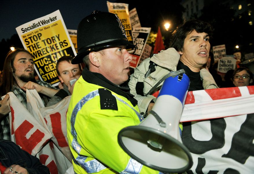 Protesters clash with police during a rally in London against spending cuts on Wednesday. Britain will slash benefits and jobs to make the largest cuts to public spending since World War II. (Associated Press)