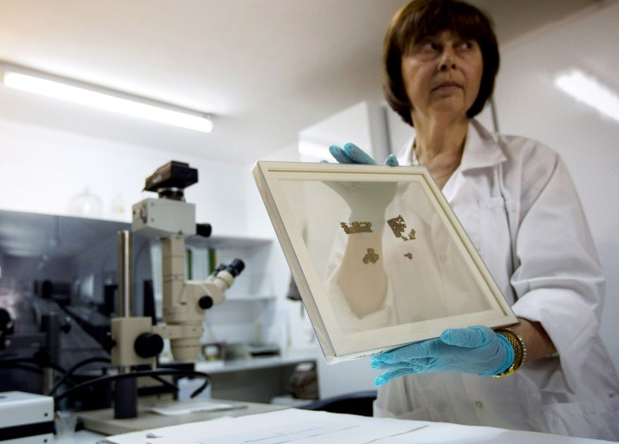 Lena Libman shows fragments of the parchment Dead Sea Scrolls in a frame at an IAA conservation laboratory. Technology may make online images of the scrolls easier to read than the originals. (Associated Press)