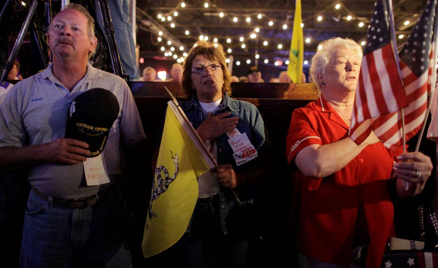 Patrick Mooney, his wife, Joan Mooney (center), and another woman sing the national anthem at the start of a Tea Party Express rally on Tuesday in Las Vegas. The Tea Party Express bus is on the second day of its 29-stop tour. It will cross 20 states before ending up in Concord, N.H., on Nov. 1. (Associated Press)