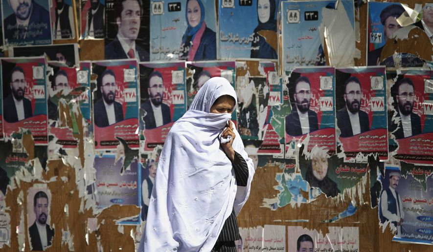 An Afghan woman walks past election posters of parliamentarian candidates in Kabul, Afghanistan on Wednesday, Sept. 22, 2010. Afghan authorities said it was too early to judge the validity of the country's parliamentary ballot despite observers' reports of widespread fraud in the vote that was to help consolidate its shaky democracy. (AP Photo/Musadeq Sadeq)