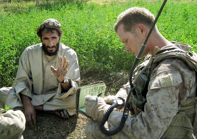 Sgt. John Gabbard of Hubert, N.C., tries to gather information from a resident of Marjah, Afghanistan. Military patrols say the locals often won't acknowledge that there are any Taliban in the area. (Associated Press)