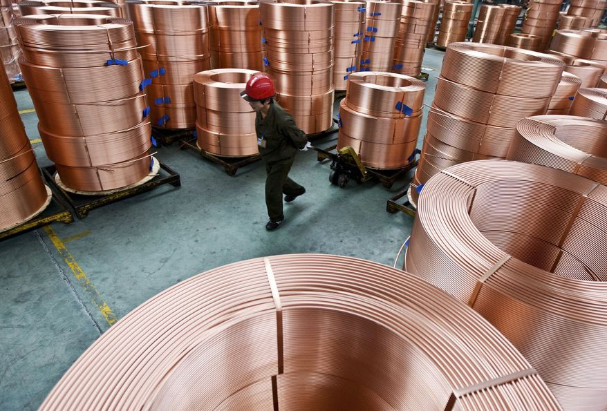 **FILE** In this photo from Sept. 29, 2010, a worker moves piles of brass tubes at a factory in Zhuji, in east China's Zhejiang province. (Associated Press)