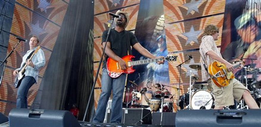FILE - In this Sept. 7, 2003 file photo, Hootie & The Blowfish perform during the Farm Aid 2003 concert at Germain Amphitheater in Columbus, Ohio. Pictured from left to right are: Dean Felber, Darius Rucker and Mark Bryan. A group of businesses in Columbia, S.C., plans to unveil a permanent piece of public art to honor the band on Thursday, Oct. 21, 2010. (AP Photo/Chris Putman, File)