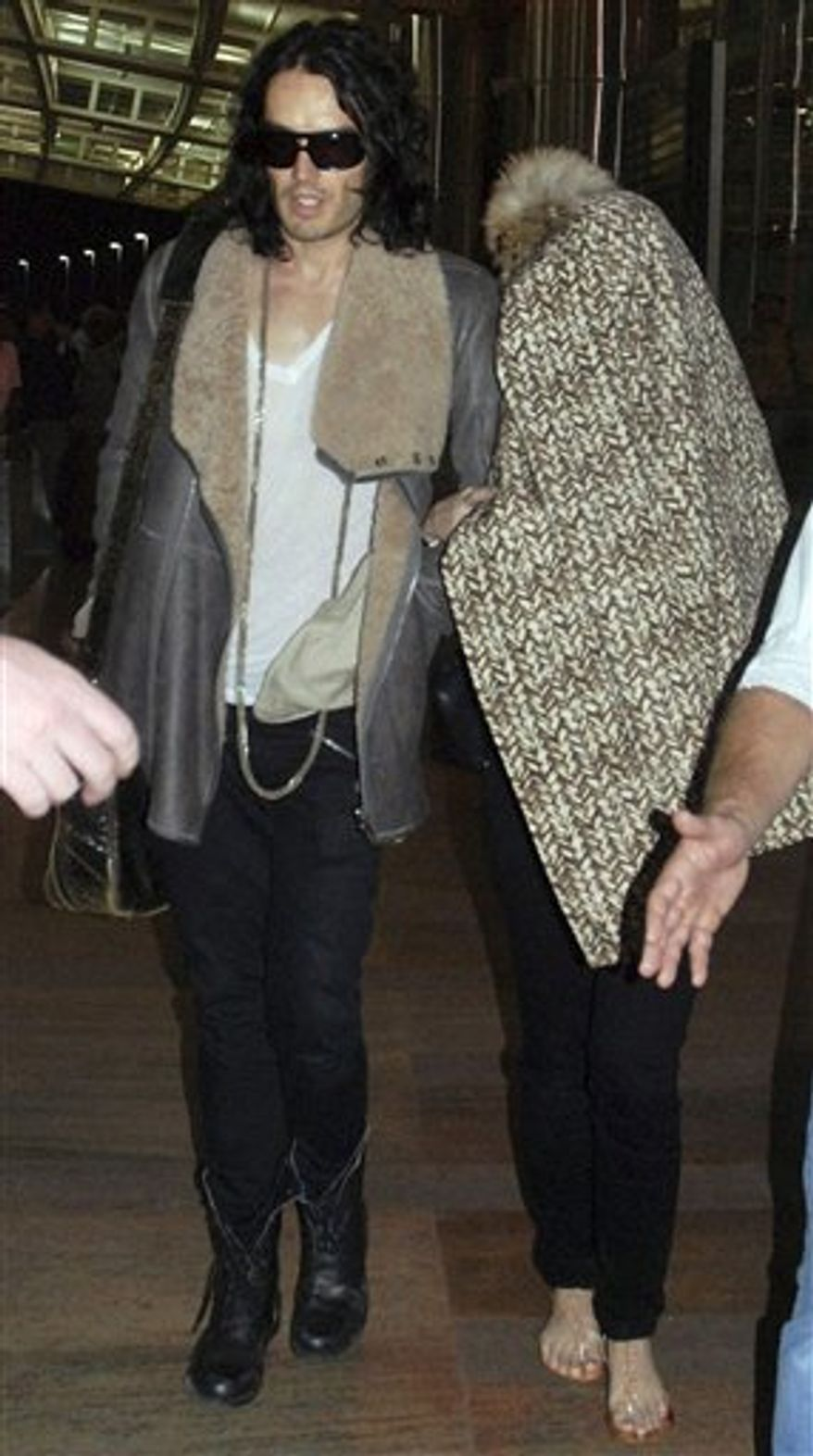 In this photo taken Wednesday, Oct. 20, 2010, British actor-comedian Russell Brand, left, walks with his fiance Katy Perry, face covered with a coat, after their arrival at the airport in Jaipur, India, Brand and Perry are reportedly to be married later this week in the northern Indian town of Jaipur. (AP Photo)
