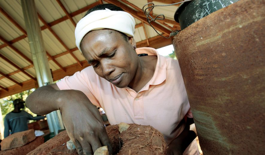 The Rev. Appolonia Okwu of Nigeria works to build a fire in her hand-built mud-and-straw brick oven in Lineville, Ala., on Oct. 5. She is one of 19 trainees from 10 countries learning how to make the efficient, clean-burning cook stoves from mud bricks. (Associated Press)