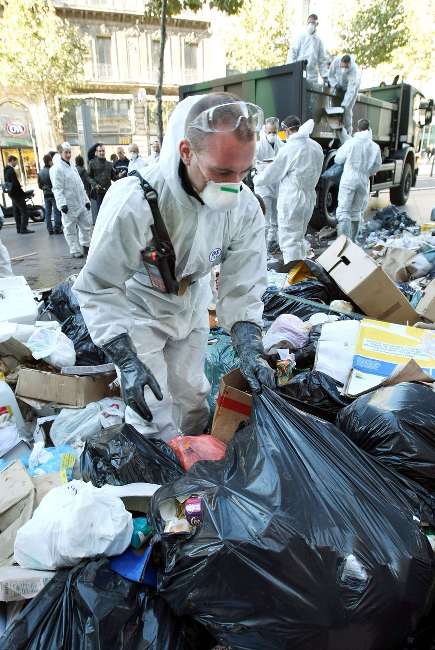 Civil security soldiers (left) collect garbage in central Marseille on Wednesday. The garbage collectors are on strike for nine days to protest against Mr. Sarkozy's plan to raise the retirement age to 62. (Associated Press)