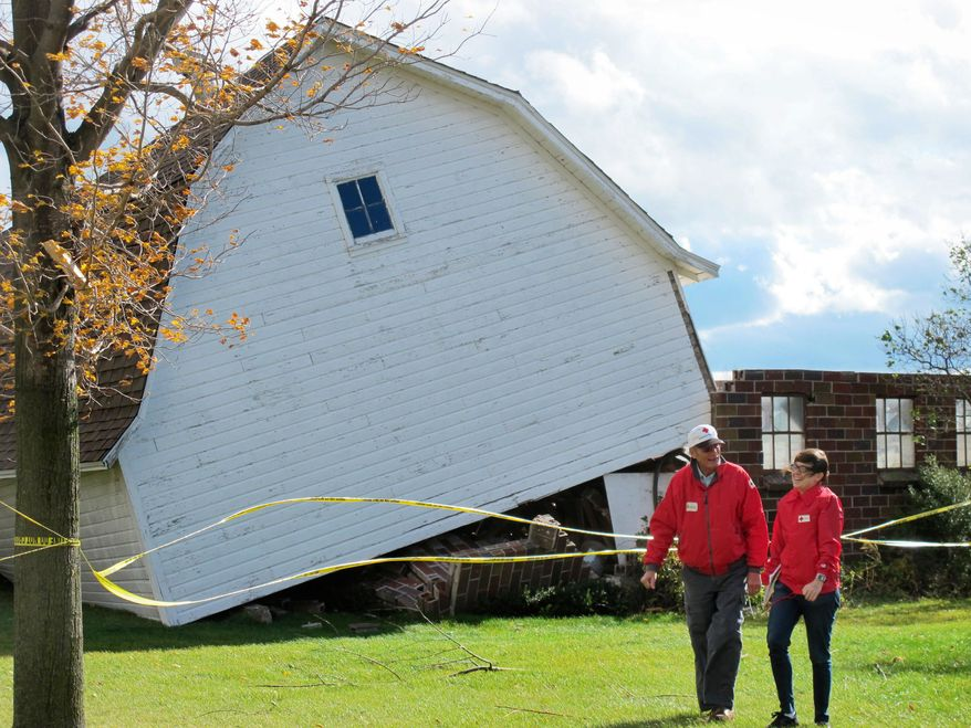 Two Red Cross workers pass a barn knocked off its foundation Tuesday in Mount Pleasant, Wis. A high-wind-and-rain storm blew through several states in the Midwest. Flights were delayed at O'Hare International Airport in Chicago. (Associated Press)