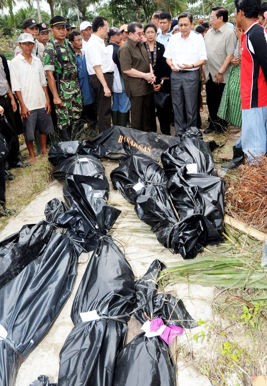 Indonesian Vice President Boediono (upper right with white shirt) looks at the bodies of tsunami victims in Pagai Utara, Mentawai Islands, on Wednesday. (Associated Press)