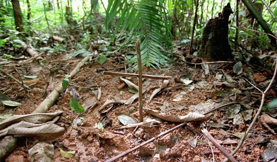 A cross marks graves near a refugee camp, about 25 miles south of Kisangani, Congo, in May 1997. The discovery of mass graves spurred probes that led to a U.N. report, which accuses invading Rwandan troops of killing tens of thousands of Hutus in 1996 and 1997. (Associated Press)